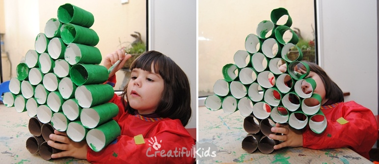 Painting a Christmas tree kids crafts from toilet rolls